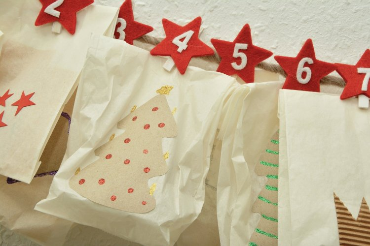 Adventskalendersäckchen aufgehangen an einer Schnur verschlossen mit kleinen Klammern