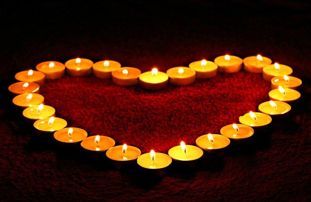 Herz aus brennenden Teelichtern