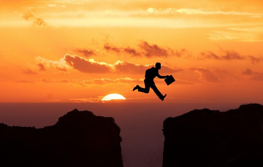Silhouette eines Mannes mit Koffer in der Hand der über eine Schlucht vom einen Gipfel zum anderen springt