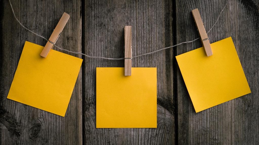 Drei gelbe, unbeschriebene Notizzettelchen mit Wäscheklammern an ein Band geheftet