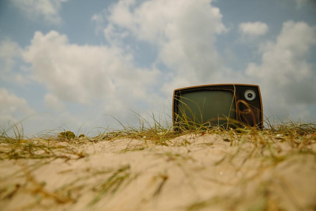 Alter Fernseher im Freien auf einer Sanddüne