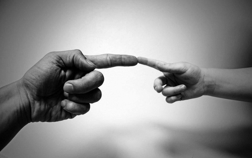 Eine Erwachsenenhand und eine Kinderhand die sich mit der Spitze des ausgestreckten Zeigefingers berühren