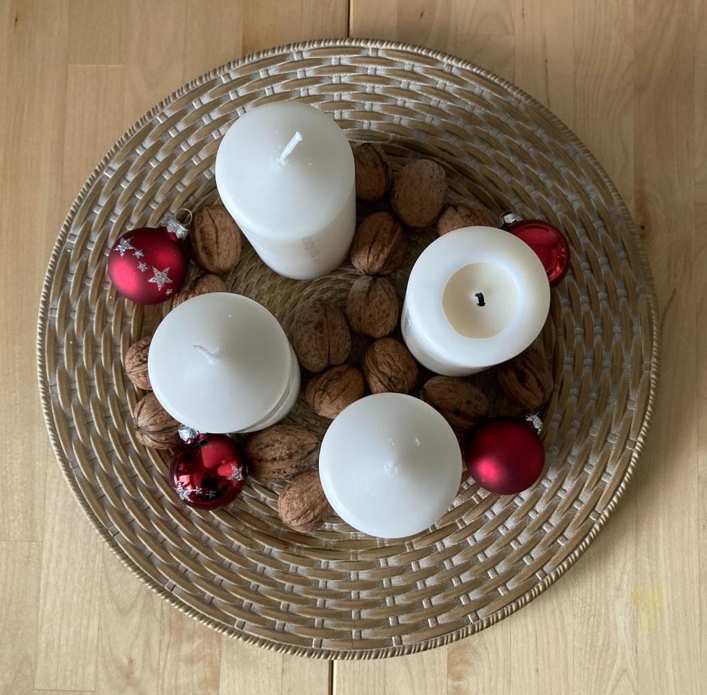 Vier weiße dicke Kerzen auf einem Teller mit Nüssen und roten Christbaumkugeln