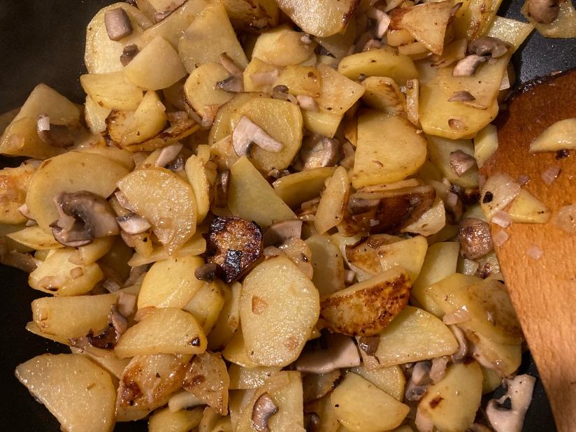 Bratkartoffeln mit Zwiebeln und Champignons in der Pfanne