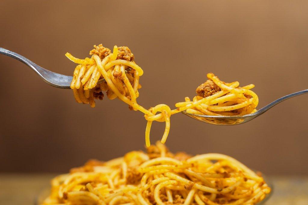 Eine Gabel und ein Löffel mit jeweils einer Portion Spaghetti durch zwei verknotete Spaghetti verbunden