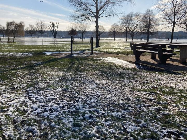 Schneebedeckte Wiese, gefrorene Pfützen und Sonnenschein
