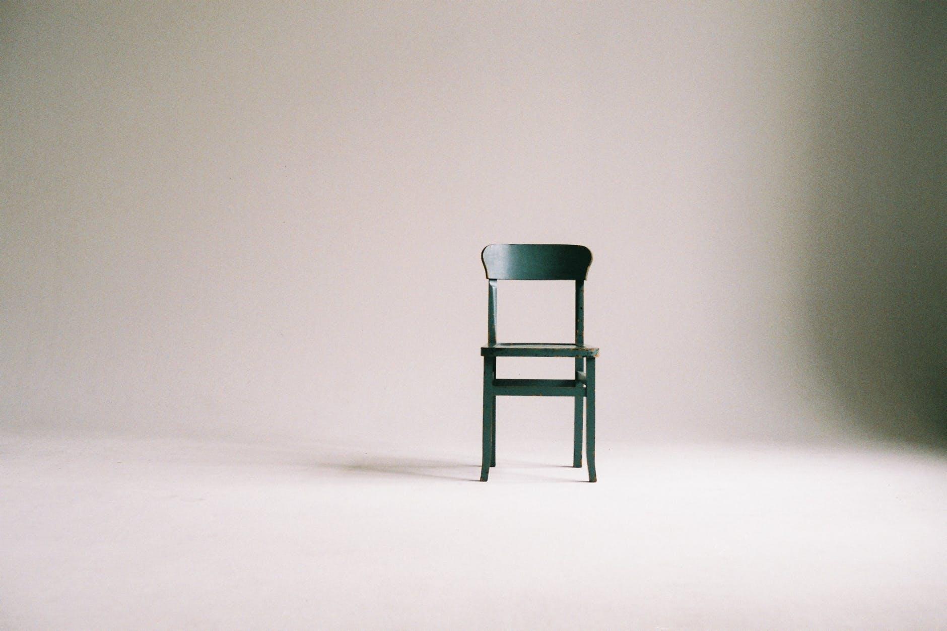 Grüner Stuhl vor einer leeren weißen Wand