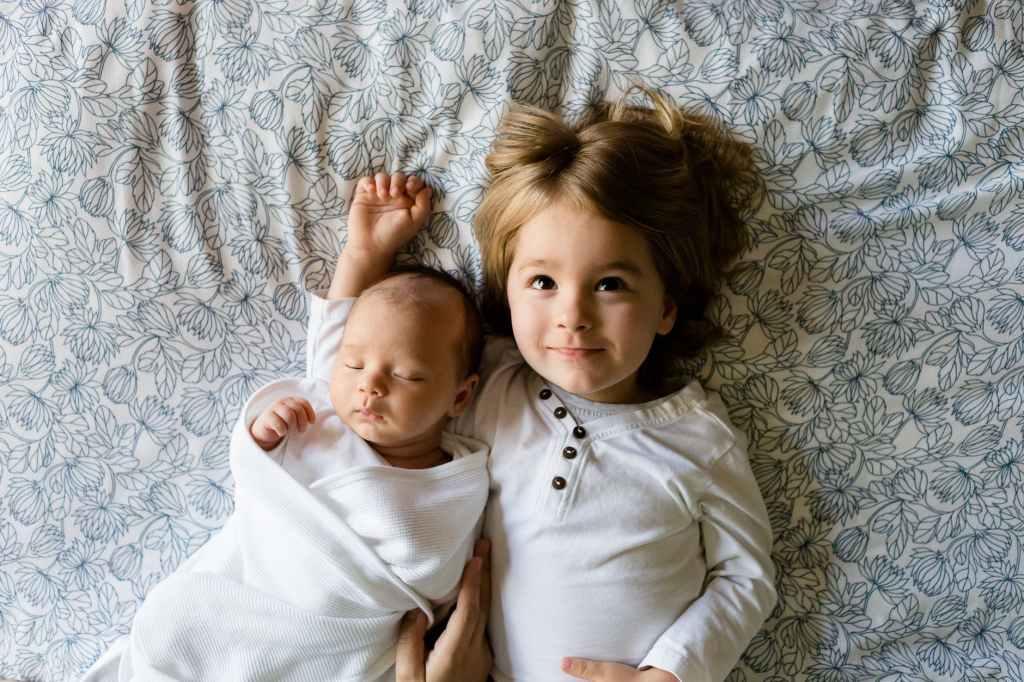 Kleinkind und Baby nebeneinander auf gemustertem Tuch