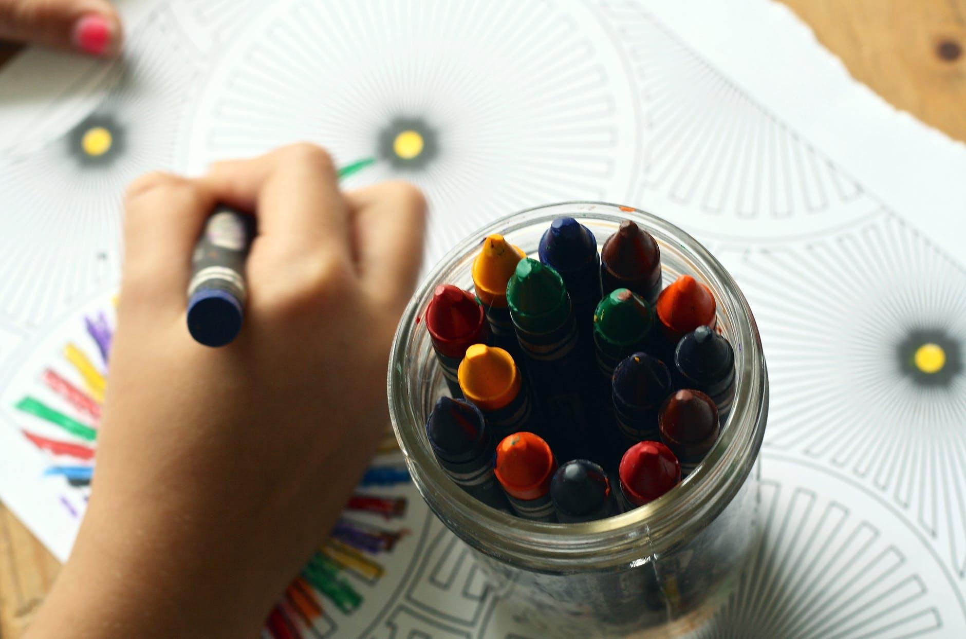Wachsmalstifte im Glas bene einer malenden Kinderhand