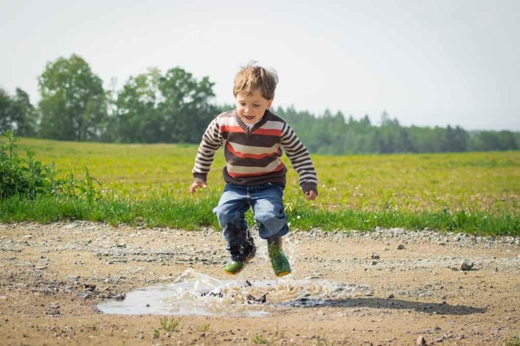 Kleiner Junge springt in eine Pfütze