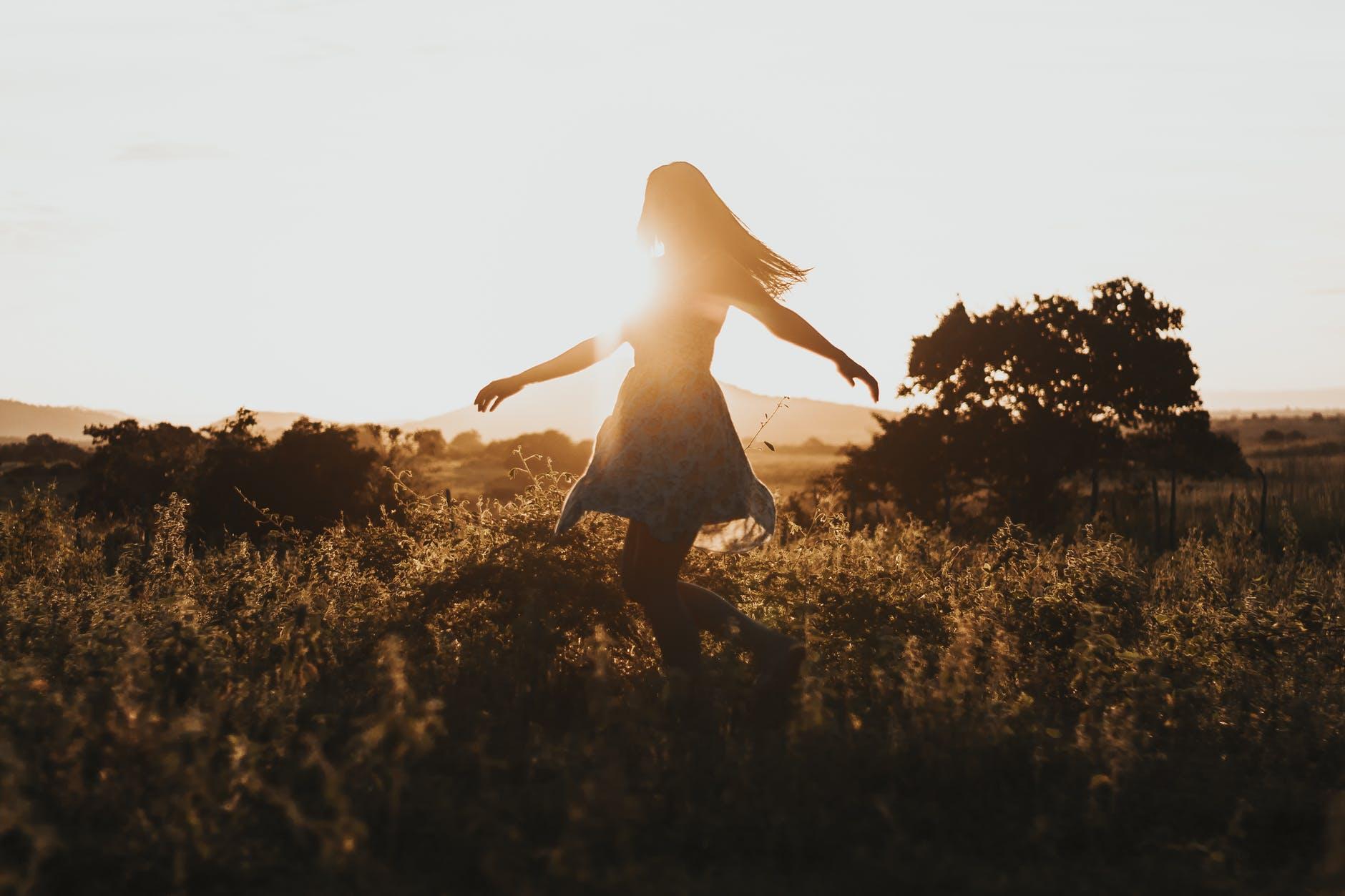 Frau im Sonnenuntergang auf einer Wiese tanzend