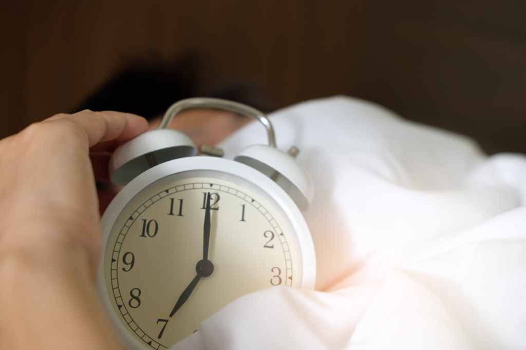 White Old School Alarm clock showing seven o'clock