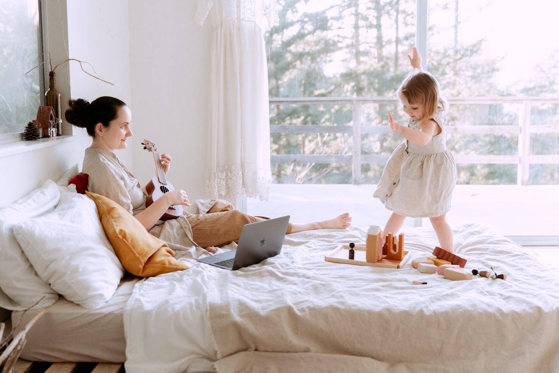 Mutter spielt mit Mädchen im Bett
