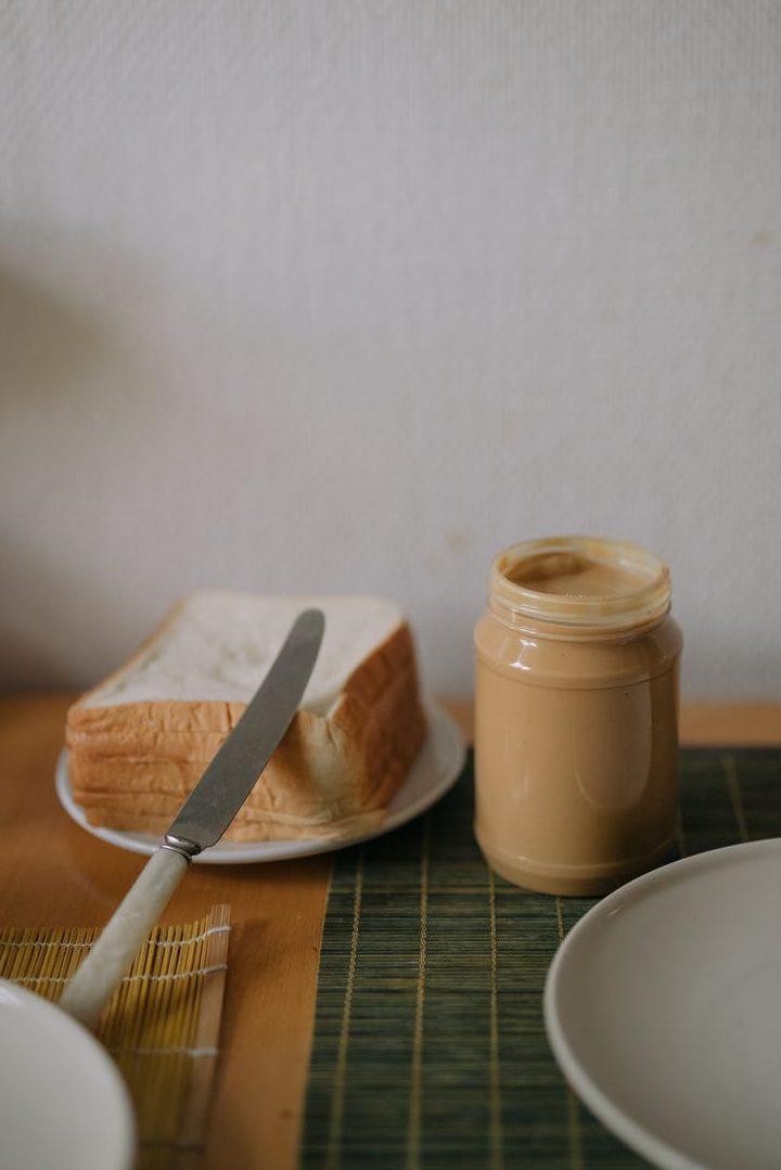Erdnussbutterglas neben einem Teller mit Toastscheiben und einem Messer drauf