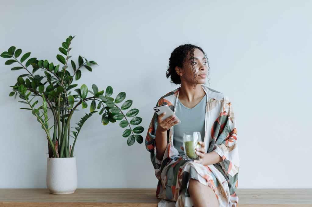 Frau mit Smartphone und Kerze in der Hand. Neben einer Pflanze sitzend.