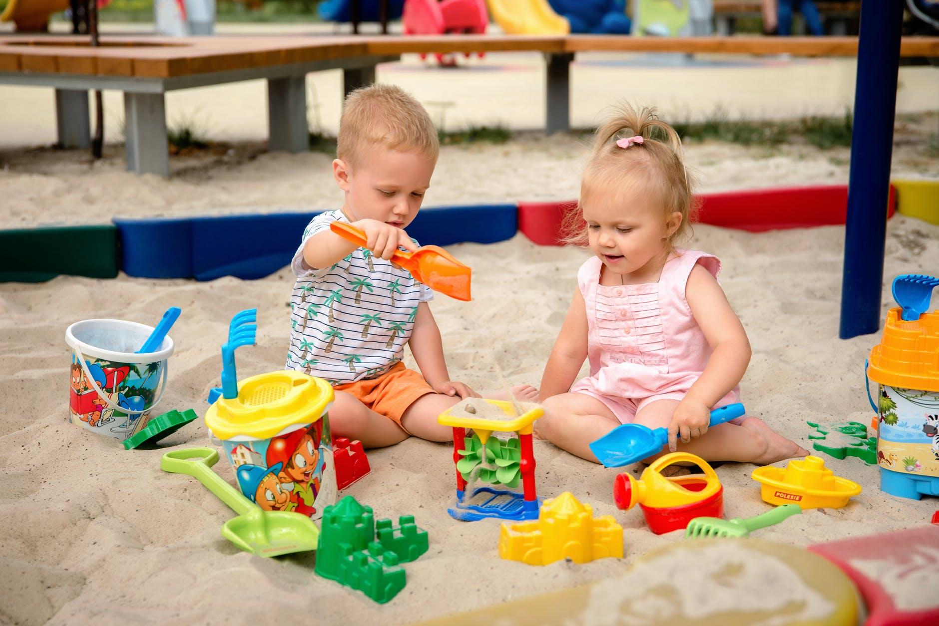 Zwei Kinder spielen im Sand mit Sandspielzeug.