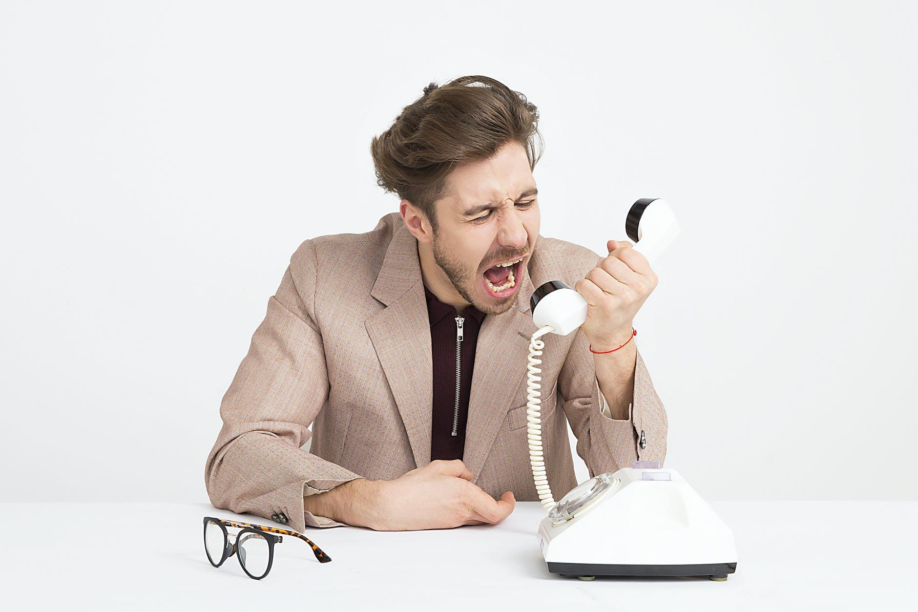 Ein Mann der in einen weißen Telefonhörer schreit.