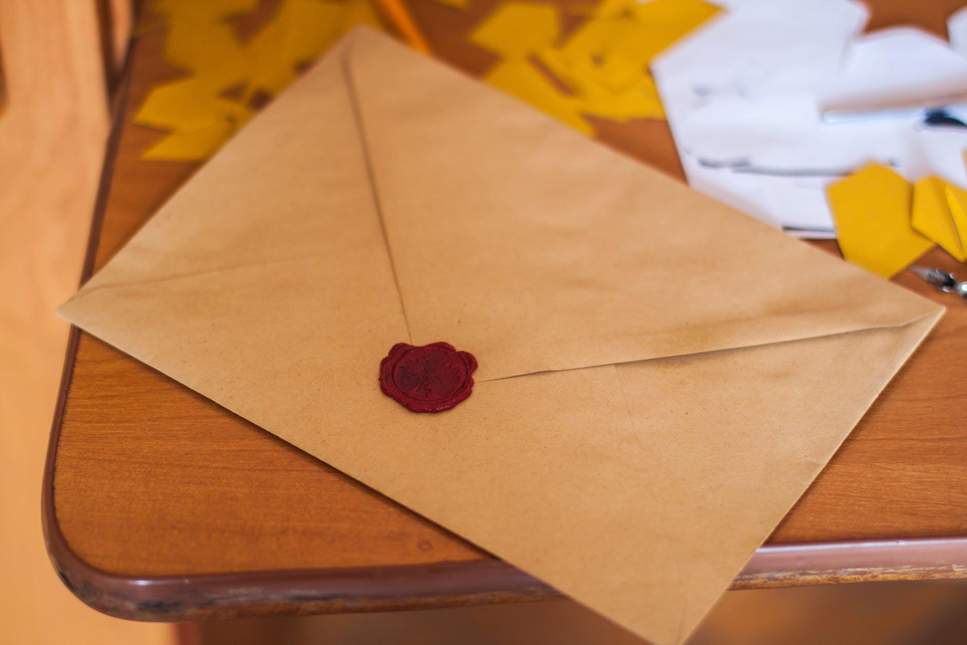 Briefumschlag auf der Ecke eines Tisches, mit rotem Wachs versiegelt.