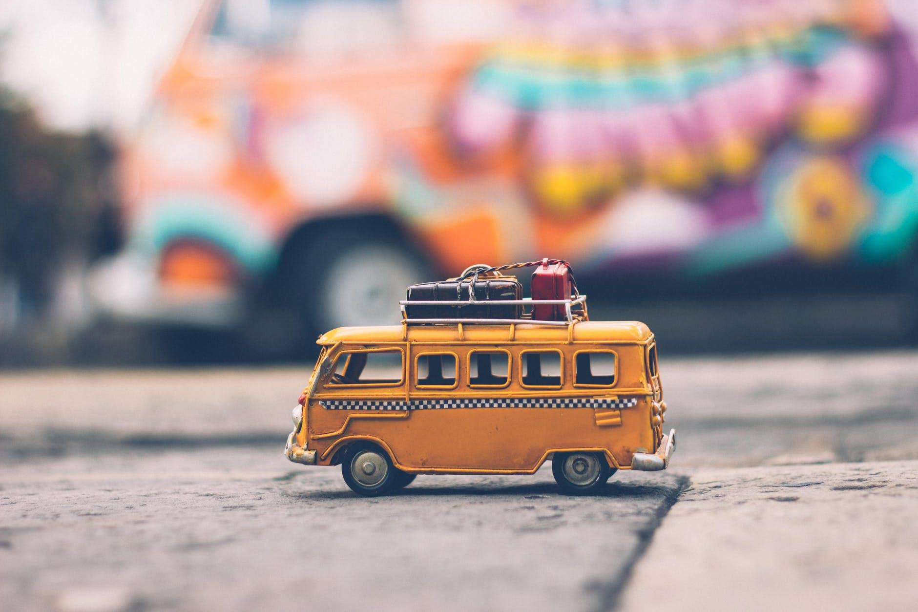 Gelber Spielzeugbus mit Koffern obendrauf